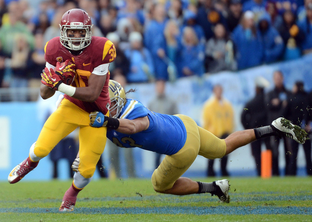 . D.J. Morgan #30 of the USC Trojans tries to break the tackle of Damien Holmes #43 of the UCLA Bruins during a 38-28 loss to the UCLA Bruins at Rose Bowl on November 17, 2012 in Pasadena, California.  (Photo by Harry How/Getty Images)