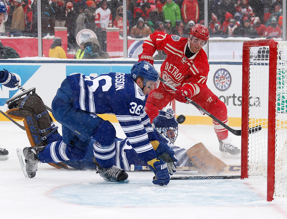 . Carl Gunnarsson #36 of the Toronto Maple Leafs looks to the clear the puck in front of fallen goalie Jonathan Bernier #45 and Daniel Cleary #71 of the Detroit Red Wings during the 2014 Bridgestone NHL Winter Classic at Michigan Stadium on January 1, 2014 in Ann Arbor, Michigan. (Photo by Gregory Shamus/Getty Images)