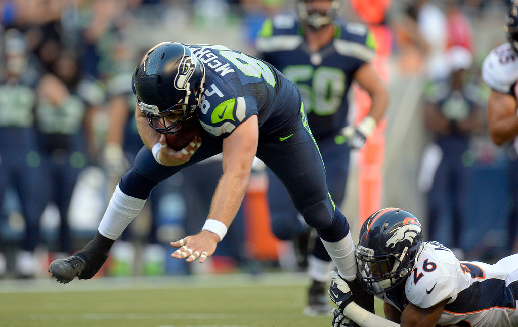 . SEATTLE, WA. - AUGUST 17: Seattle Seahawks tight end Sean McGrath (84) gets tripped up by Denver Broncos free safety Rahim Moore (26) after a gain during the first quarter August 17, 2013 at Century Link Field. (Photo By John Leyba/The Denver Post)
