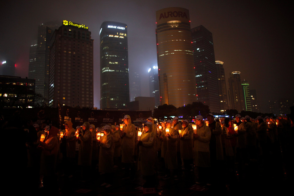 ". People hold candles during an event attempting to establish a Guinness world record for ""blowing out the most number of candles simultaneously\"" during Earth Hour in Shanghai March 23, 2013. Earth Hour, when everyone around the world is asked to turn off lights for an hour from 8.30 p.m. local time, is meant as a show of support for tougher actions to confront climate change. REUTERS/Carlos Barria"