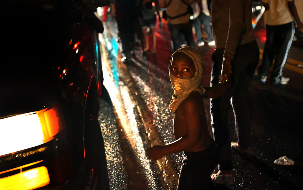 . Isaiah King Ivy, 3, makes his shirt a mask as he participates in demonstrations with his north St. Louis County family on West Florissant Avenue in Ferguson on Friday, Aug. 15, 2014.  (AP Photo/St. Louis Post-Dispatch, Robert Cohen)