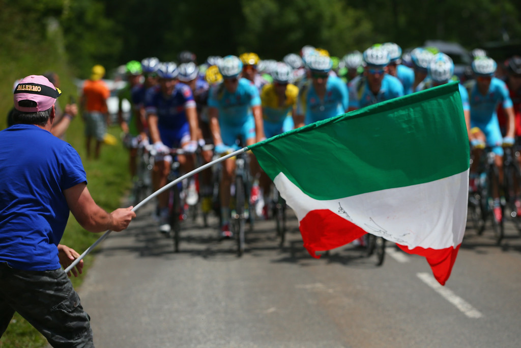 . A fan waves an Italian flag as Vincenzo Nibali of Italy and the Astana Pro Team defends the overall race leader\'s yellow jersey with the protection of his teammates in the peloton on the climb of the Col de Portet d\'Aspet during the sixteenth stage of the 2014 Tour de France, a 238km stage between Carcassonne and Bagneres-de-Luchon, on July 22, 2014 in Portet d\'Aspet, France.  (Photo by Doug Pensinger/Getty Images)