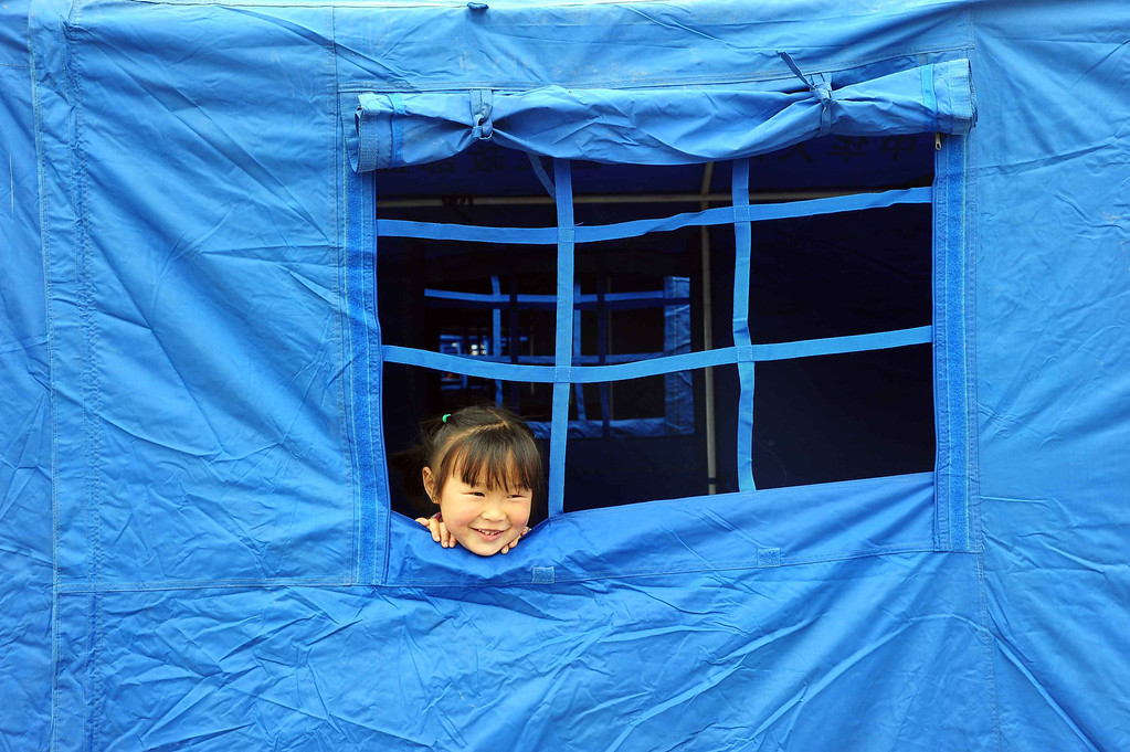 . A little girl looks on from the window of a tent in the temporary settlement in Longmen township, a town close to the epicentre of the earthquake that hit the city in Ya\'an, southwest China\'s Sichuan province on April 21, 2013.  AFP PHOTO    STR/AFP/Getty Images
