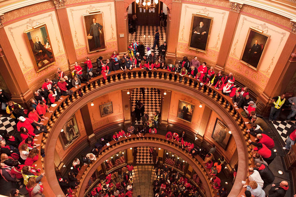 . Labor union members and supporters hang a flag in the Capitol rotunda as they demonstrate in opposition to a proposed right-to-work measure inside the capitol building in Lansing, Michigan December 11, 2012.  Michigan legislators on Tuesday approved laws that ban mandatory membership in public and private sector unions, dealing a stunning blow to organized labor in the home of the U.S. auto industry.  REUTERS/James Fassinger