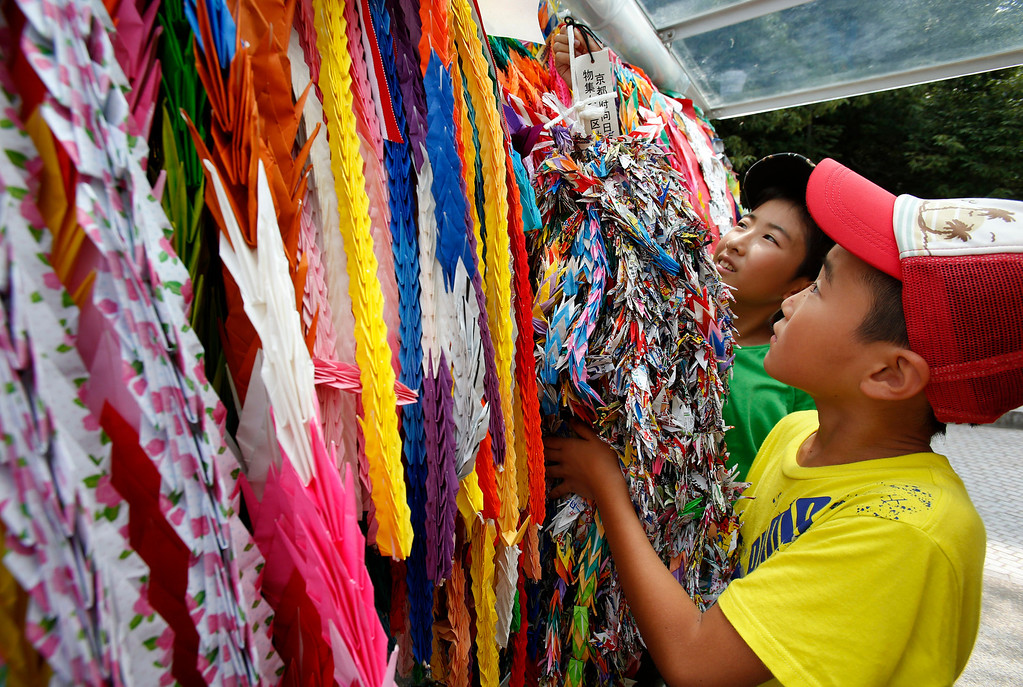 . Masaki Namikawa, 11, left, and Keita Deguchi, 9, hang a bundle of paper cranes to add on to thousands of them already placed as a symbolic act dedicated from across the world for world peace at Hiroshima Memorial Peace Park in Hiroshima, western Japan, Monday, Aug. 5, 2013. (AP Photo/Shizuo Kambayashi)