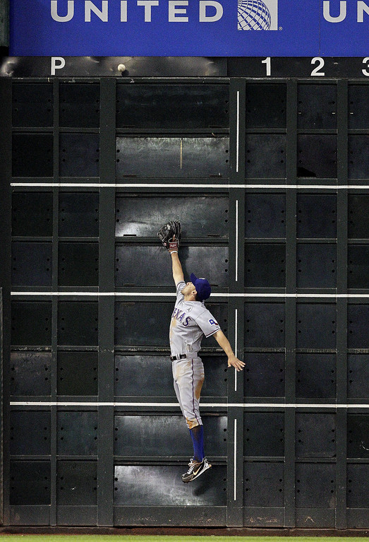 . Ian Kinsler #5 of the Texas Rangers leaps at the wall but can\'t make a catch on a ball hit by Justin Maxwell #44 of the Houston Astros on Opening Day at Minute Maid Park on March 31, 2013 in Houston, Texas.  (Photo by Bob Levey/Getty Images)