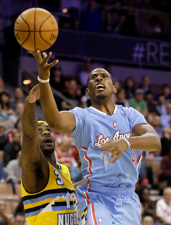 . The Los Angeles Clippers\' Chris Paul, right, shoots over the Denver Nuggets\' Ty Lawson during the first half of a preseason NBA basketball game on Saturday, Oct. 19, 2013, in Las Vegas. The Clippers defeated the Nuggets in overtime 118-111. (AP Photo/Isaac Brekken)