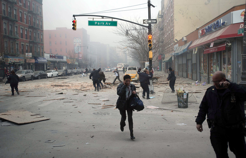 . People run after an explosion and building collapse in the East Harlem neighborhood of New York, Wednesday, March 12, 2014. T (AP Photo/Jeremy Sailing)