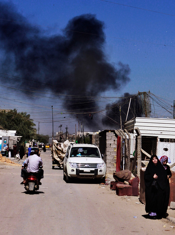 . Smoke rises after a car bomb attack in Sadr City, Baghdad, Iraq, Tuesday, March 19, 2013.  (AP Photo/ Karim Kadim)