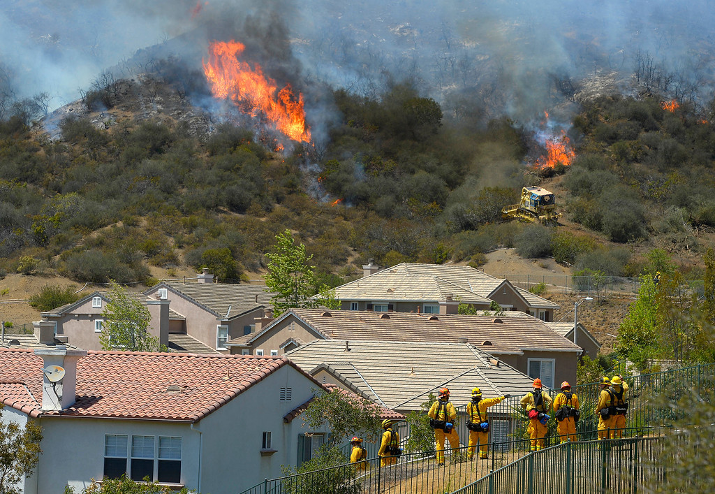 . Firefighters stand watch as bulldozers clear a firebreak near a wildfire burning along a hillside near homes in Thousand Oaks, Calif., Thursday, May 2, 2013.  (AP Photo/Mark J. Terrill)