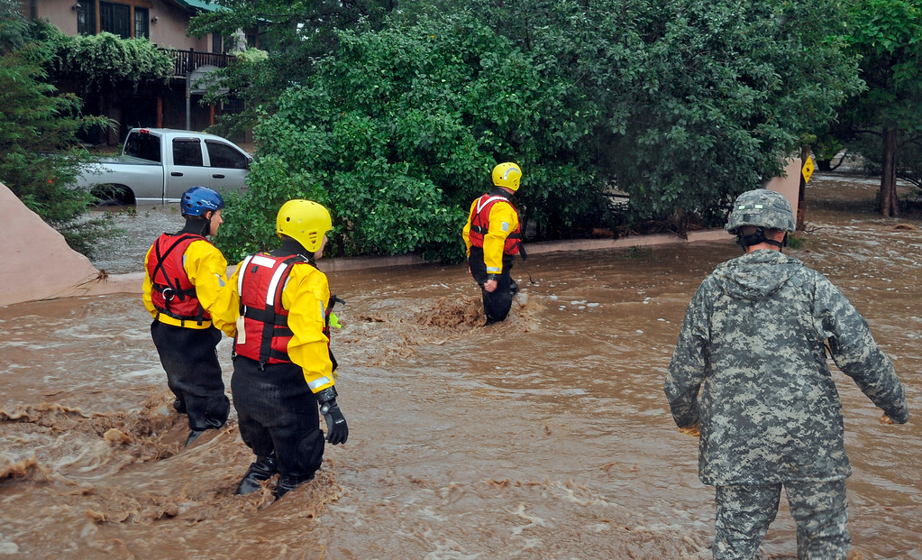 . In this photo provided by the Colorado National Guard, guardsmen, including water rescue specialists in red vests, search a flooded neighborhood in Lyons, Colo., Thursday, Sept. 12, 2013.  (AP Photo/Army National Guard, Sgt. Joseph K. VonNida)