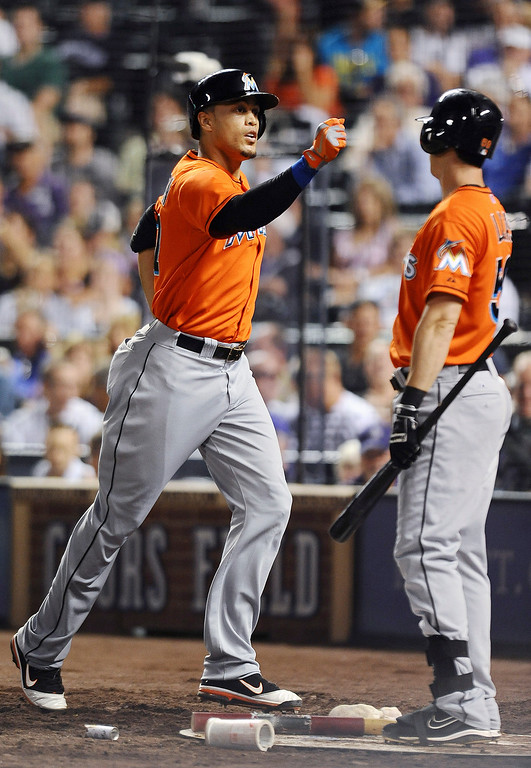 . Miami Marlins\' Giancarlo Stanton, left, is congratulated by Ed Lucas after hitting a solo home run in the eighth inning of a baseball game against the Colorado Rockies on Tuesday, July 23, 2013, in Denver. (AP Photo/Chris Schneider)