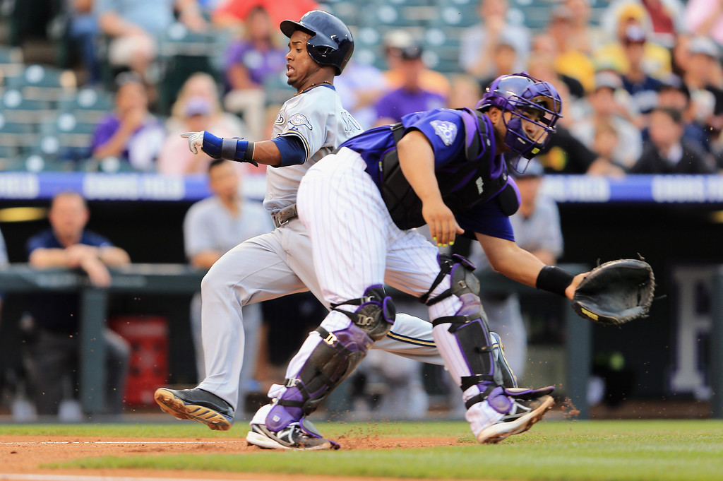 . DENVER, CO - JULY 27:  Jean Segura #9 of the Milwaukee Brewers scores behind catcher Wilin Rosario #20 of the Colorado Rockies on a sacrifice fly by Carlos Gomez #27 of the Milwaukee Brewers against starting pitcher Collin McHugh #43 of the Colorado Rockies in the first inning at Coors Field on July 27, 2013 in Denver, Colorado.  (Photo by Doug Pensinger/Getty Images)