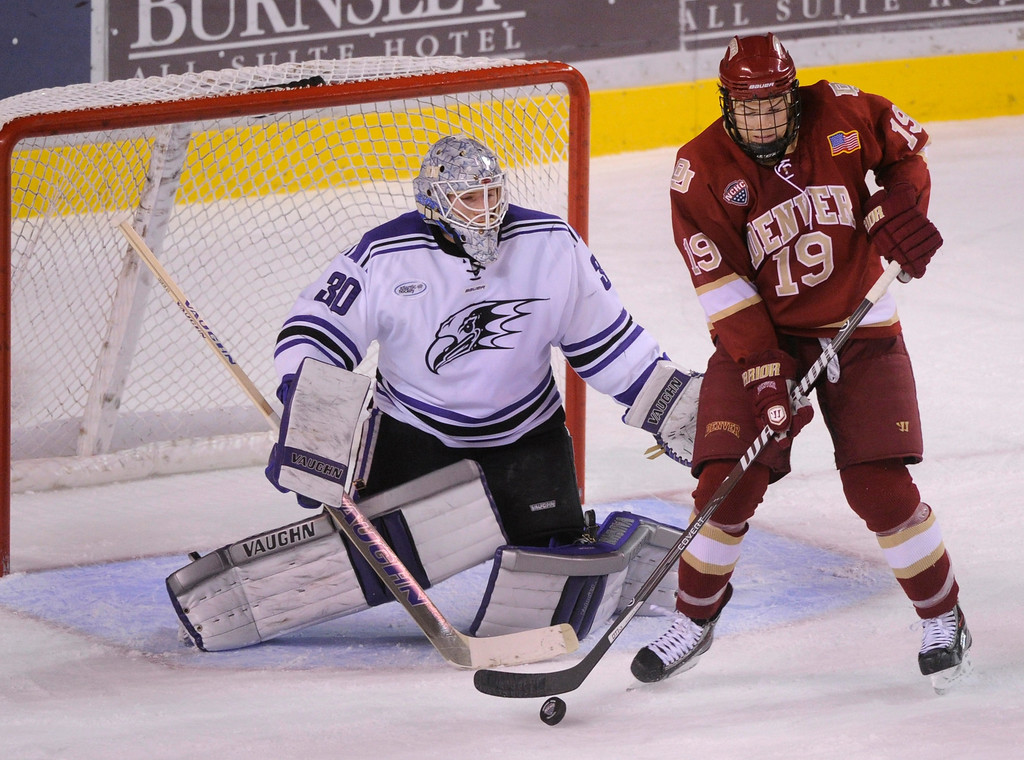 . DENVER, CO. - OCTOBER 25: Denver center Daniel Doremus (19) tried to deflect a shot past Niagara goaltender Jackson Teichroeb (30) in the first period. The University of Denver hockey team hosted Niagara at Magness Arena Friday night, October 25, 2013. Photo By Karl Gehring/The Denver Post
