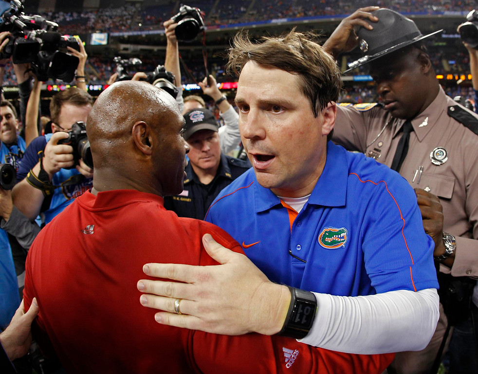 . Louisville Cardinals head coach Charlie Strong (L) speaks with Florida Gators head coach Will Muschamp after the Cardinals defeated the Gators in the 2013 Allstate Sugar Bowl NCAA football game in New Orleans, Louisiana January 3, 2013.  REUTERS/Jonathan Bachman