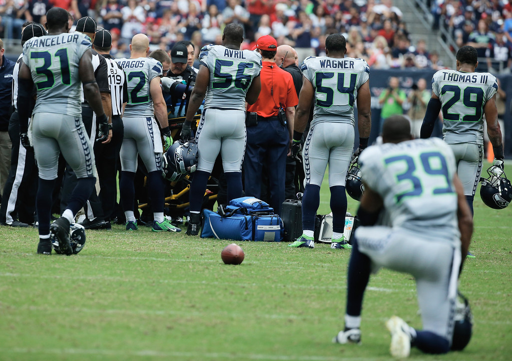 . HOUSTON, TX - SEPTEMBER 29:  Michael Bennett #72 of the Seattle Seahawks is attended to in the second quarter by medical staff as his teammates look on during the game against the Houston Texans at Reliant Stadium on September 29, 2013 in Houston, Texas.  (Photo by Scott Halleran/Getty Images)