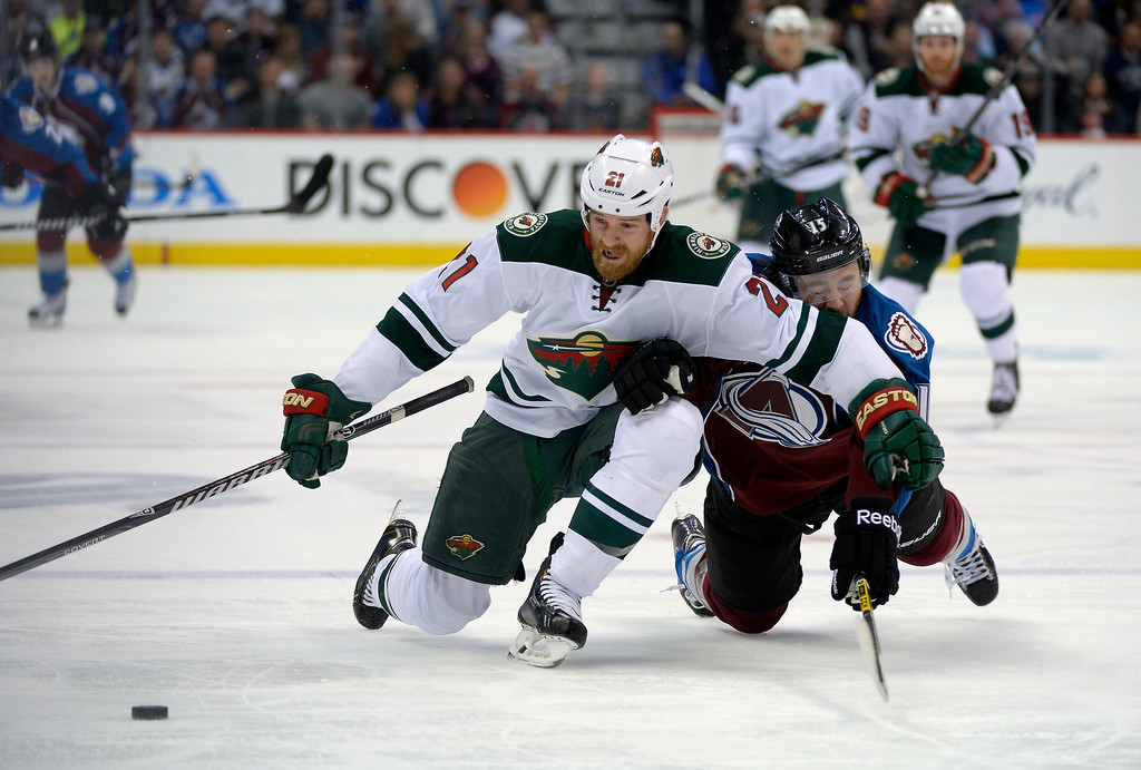 . Colorado Avalanche right wing P.A. Parenteau (15) gets taken down by Minnesota Wild center Kyle Brodziak (21) during the second period.    (Photo by John Leyba/The Denver Post)