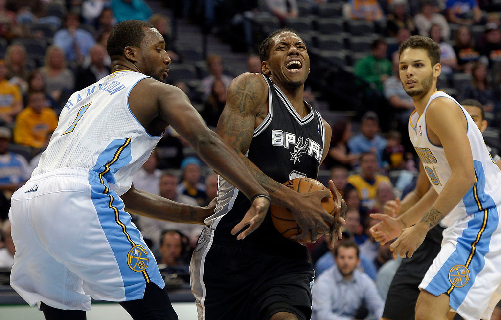 . San Antonio Spurs small forward Kawhi Leonard (2) gets fouled as he drives to the basket on Denver Nuggets shooting guard Jordan Hamilton (1) during the first quarter October 14, 2013 at Pepsi Center. (Photo By John Leyba/The Denver Post)