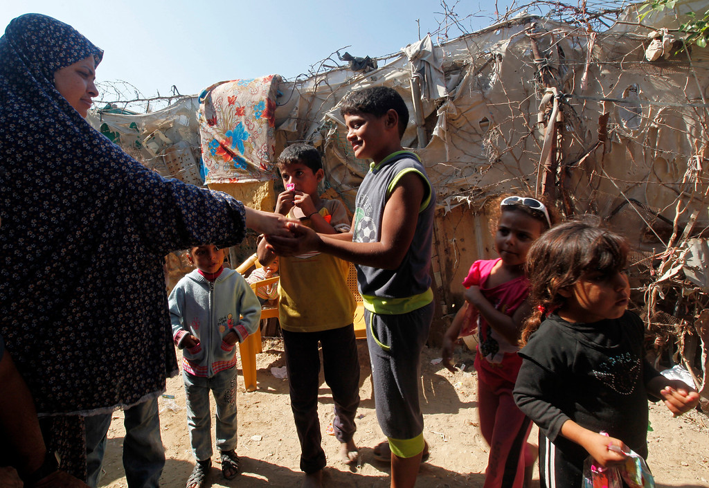 . In this Thursday, Oct. 17, 2013 photo, Om Abood Alwadiya, 36, left, gives candy to children as they celebrate on the third day of the Muslim festival of Eid al-Adha in front of their family\'s house in Gaza City. Most of the food and clothing for the 38-member extended family comes from donations. (AP Photo/Adel Hana)