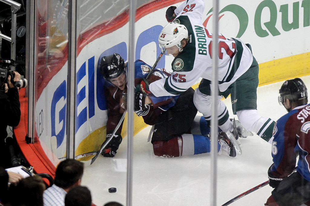 . Colorado Avalanche\'s Gabriel Landeskog (92) and Minnesota Wild\'s Jonas Brodin (25) vie for possession in the corner during the first period of an NHL hockey game Thursday, Jan. 30, 2014, in Denver. (AP Photo/Barry Gutierrez)
