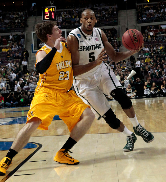 . Michigan State Spartans\' Adreian Payne (R) is defended by Valparaiso Crusaders\' Matt Kenney during the first half of their second round NCAA tournament basketball game in Auburn Hills, Michigan March 21, 2013. REUTERS/Jeff Kowalsky