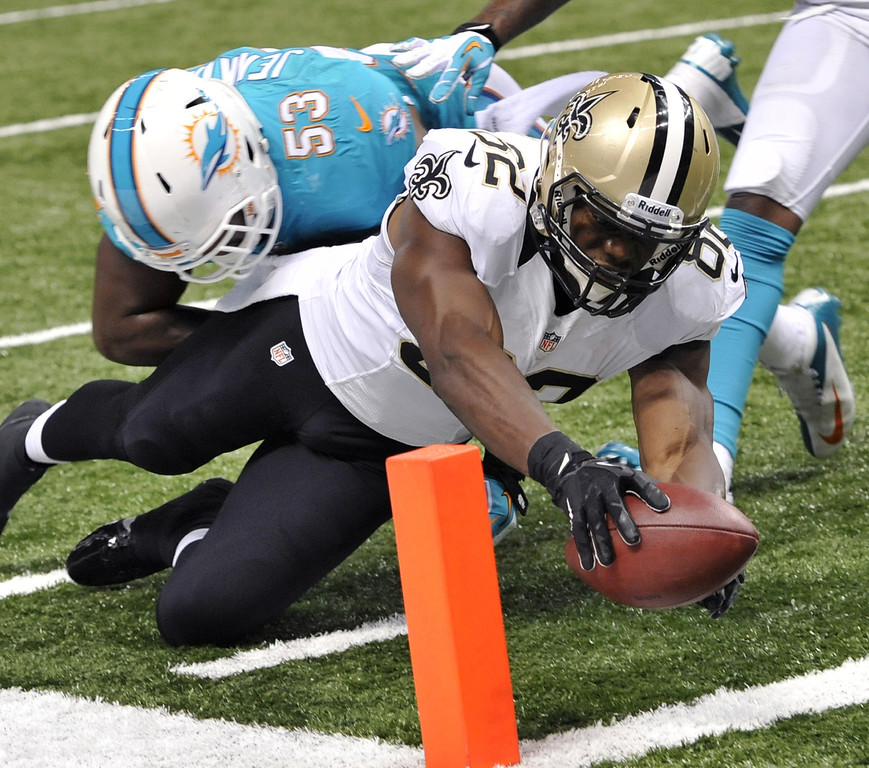 . New Orleans Saints tight end Benjamin Watson (82) reaches over the pylon to score a touchdown as Miami Dolphins\' Jelani Jenkins (53) attempts the tackle in the second half of an NFL football game in New Orleans, Monday, Sept. 30, 2013. (AP Photo/Bill Feig)