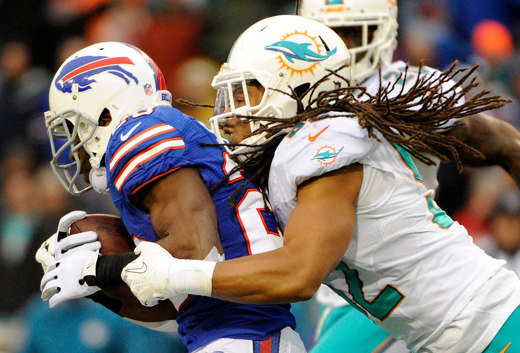 . Miami Dolphins outside linebacker Philip Wheeler, right, tackles Buffalo Bills running back C.J. Spiller (28) during the second half of an NFL football game Sunday, Dec. 22, 2013, in Orchard Park, N.Y. (AP Photo/Gary Wiepert)