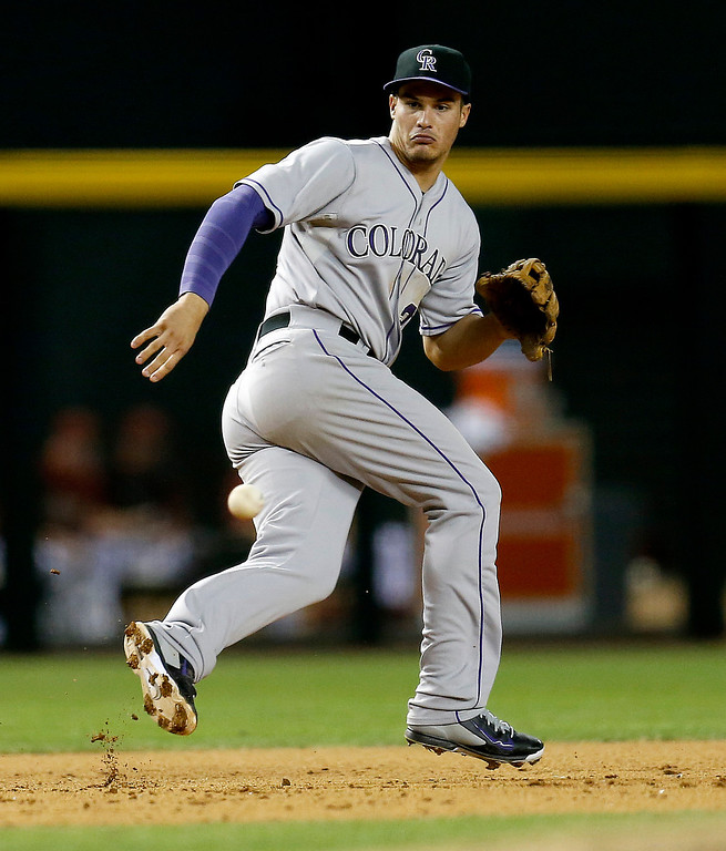 . Colorado Rockies\' Nolan Arenado chases down a ground-out by Arizona Diamondbacks\' Josh Collmenter during the fifth inning of a baseball game on Wednesday, April 30, 2014, in Phoenix. (AP Photo/Matt York)