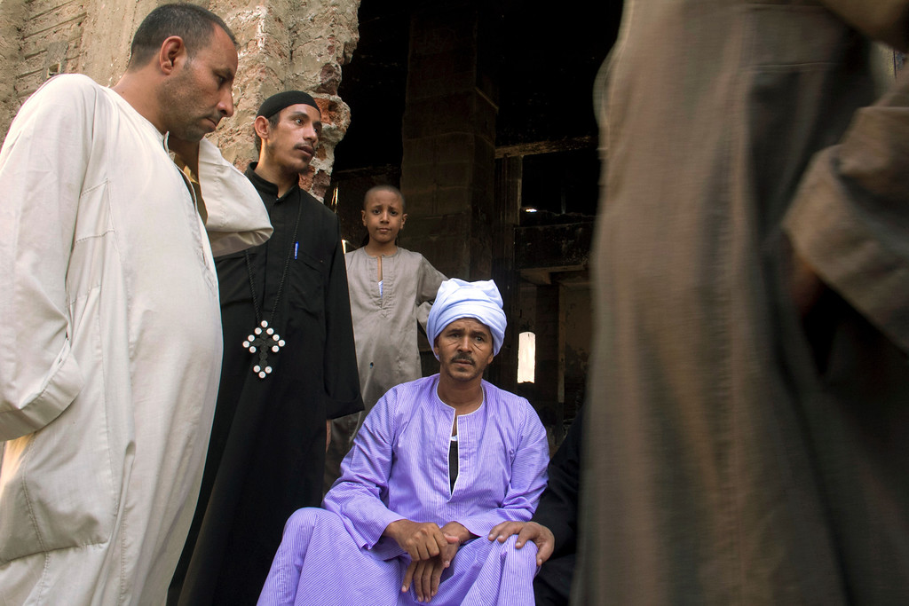 . In this Sept. 3, 2013 photo, Egyptian priest Samuel Zaki, second left, talks to villagers at the door of the main church inside the Virgin Mary and St. Abraam Monastery that was looted and burned by Islamists, in Dalga, Minya province, Egypt. Dalga has been outside government control since hard-line supporters of the Islamist Mohammed Morsi drove out police and occupied their station on July 3, the day Egypt\'s military chief removed the president in a popularly supported coup. It was part of a wave of attacks in the southern Minya province that targeted Christians, their homes and businesses. (AP Photo/El Shorouk Newspaper, Roger Anis)
