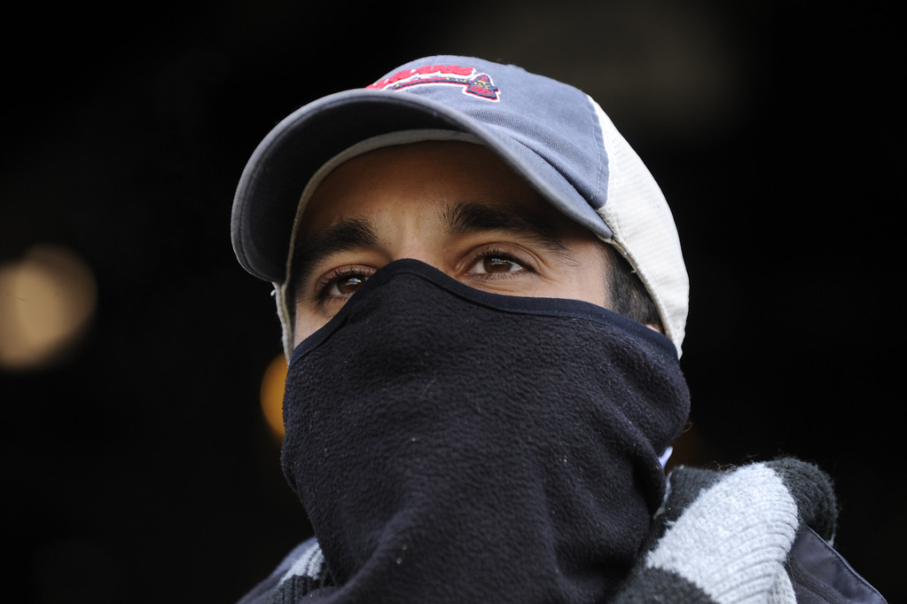 . DENVER, CO. - APRIL 23:  Atlanta fan Derek Dominguez covered his face from the cold in the ninth inning. The Atlanta Braves defeated the Colorado Rockies 4-3 at Coors Field Tuesday, April 23, 2013.  The first game of the doubleheader Tuesday was a make-up from Monday night\'s postponement due to weather.  Photo By Karl Gehring/The Denver Post