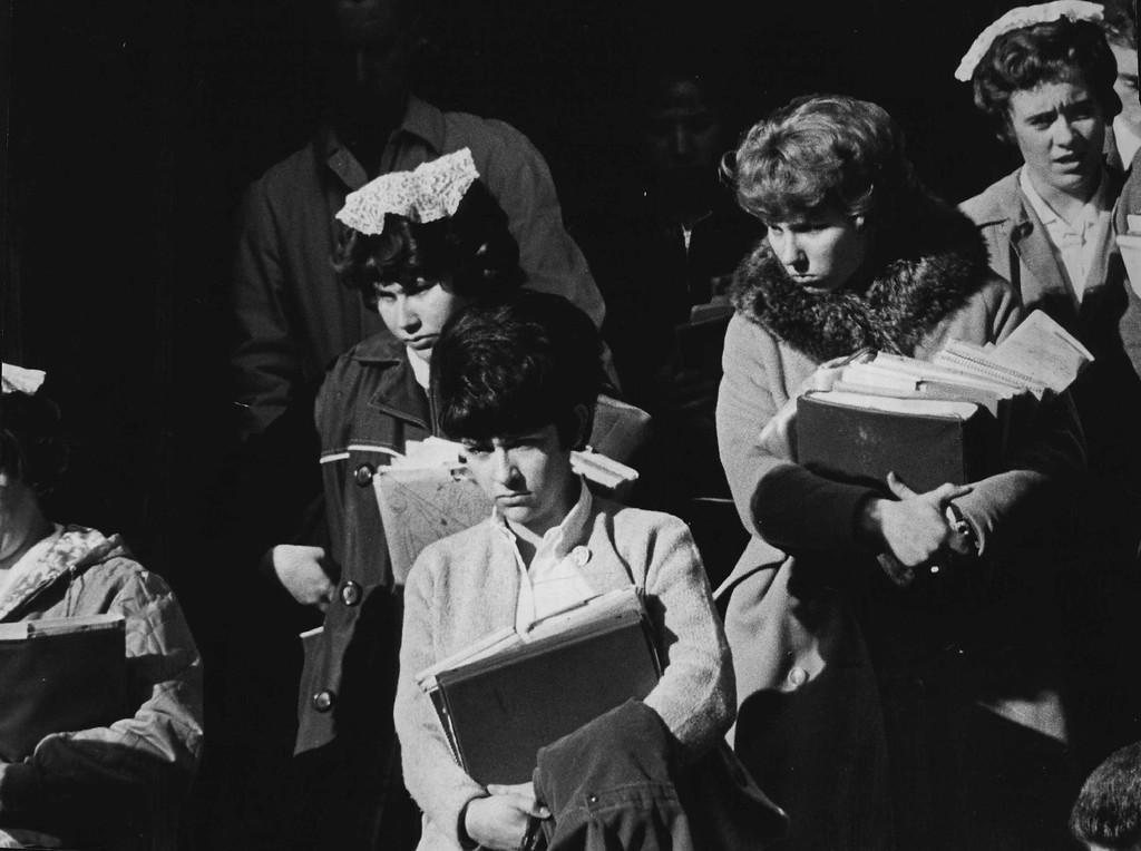 . School books in their arms, students leave Immaculate Conception Cathedral on Nov. 22, 1963, in one example of people\'s reaction in Denver as they offered  prayers for the president, his family and the nation.