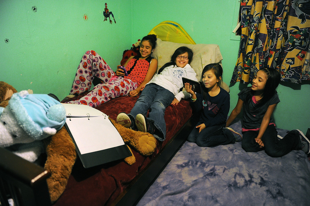 . GREELEY, CO - DECEMBER 16, 2013:  From left to right Genoveva Meza, 14, Janeth Moreno, 10, her sister Yanna, 8 and Maria, Meza, 11, all share these two beds in the tiny bedroom of the Meza\'s tiny home in Greeley, CO on December 16, 2013.  The Meza family, which consists of four children, Norma and her husband Martin have taken in the Moreno family after they lost everything in the September floods.  Rosario and her husband Jose have 5 children and are without a home at the moment.  Norma says she will help out her best friend for as long as she needs to.  The tiny house has 3 bedrooms and 2 small bathrooms and is home now to 14 people, 2 cats and 3 dogs.  (Photo By Helen H. Richardson/ The Denver Post)