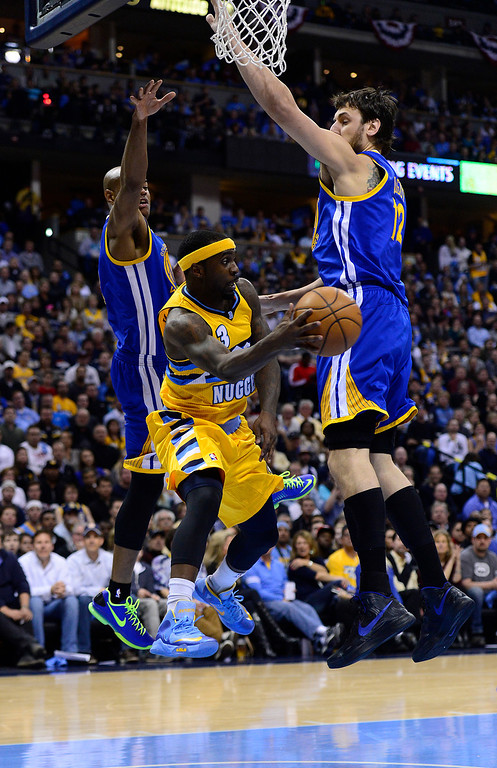 . DENVER, CO. - APRIL 23: Denver Nuggets point guard Ty Lawson (3) makes a pass under the basket while being guarded by Golden State Warriors center Andrew Bogut (12) and Golden State Warriors point guard Jarrett Jack (2) in the third quarter. The Denver Nuggets took on the Golden State Warriors in Game 2 of the Western Conference First Round Series at the Pepsi Center in Denver, Colo. on April 23, 2013. (Photo by AAron Ontiveroz/The Denver Post)