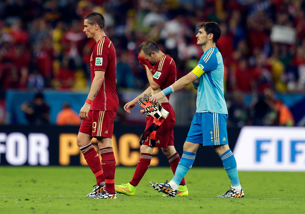 . From left, Spain\'s Fernando Torres, Andres Iniesta and goalkeeper Iker Casillas walk off the pitch following their group B World Cup soccer match between Spain and Chile at the Maracana Stadium in Rio de Janeiro, Brazil, Wednesday, June 18, 2014. Defending champion Spain was eliminated from the World Cup after losing to Chile 2-0.  (AP Photo/Natacha Pisarenko)