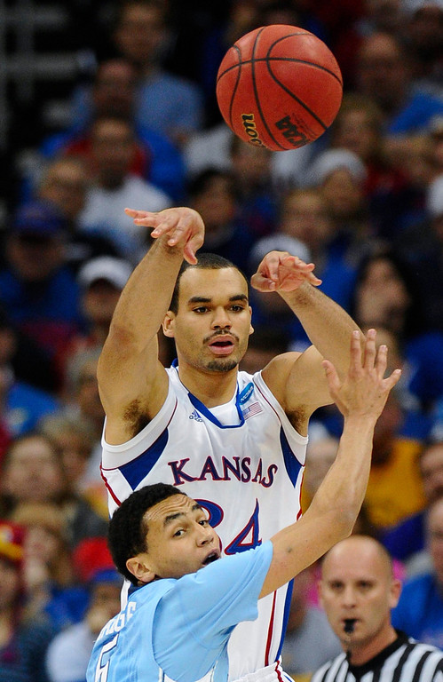 . Kansas Jayhawks forward Perry Ellis (top) passes over North Carolina Tar Heels guard Marcus Paige during the first half of the third round of the NCAA men\'s basketball tournament at the Sprint Center in Kansas City, Missouri March 24, 2013. REUTERS/Dave Kaup