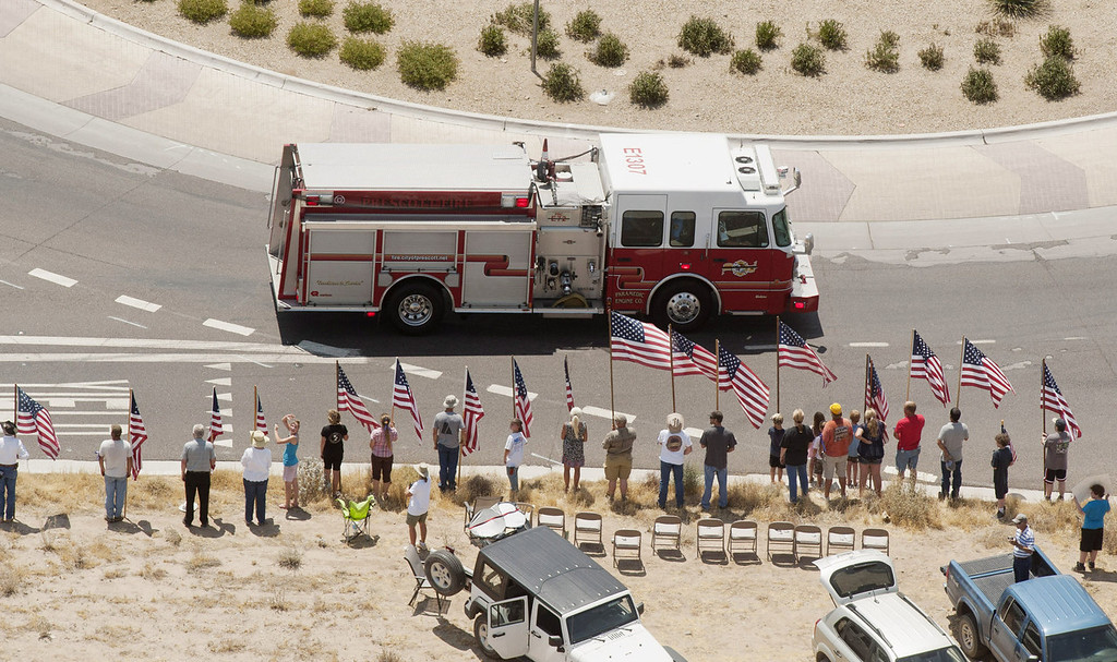 . A fire truck travels as part of the procession under escort by the Joint Arizona Honor Guard, for the 19 fallen firefighters of the Granite Mountain Hotshots crew on July 7, 2013 in Phoenix, Arizona. The firefighters are transported by 19 hearses, each accompanied by motorcycle escorts from various agencies from Phoenix, Arizona to Prescott, Arizona. Nineteen of the twenty member crew died battling a fast-moving wildfire near Yarnell, Arizona on Sunday June 30th. (Photo by Laura Segall/Getty Images)