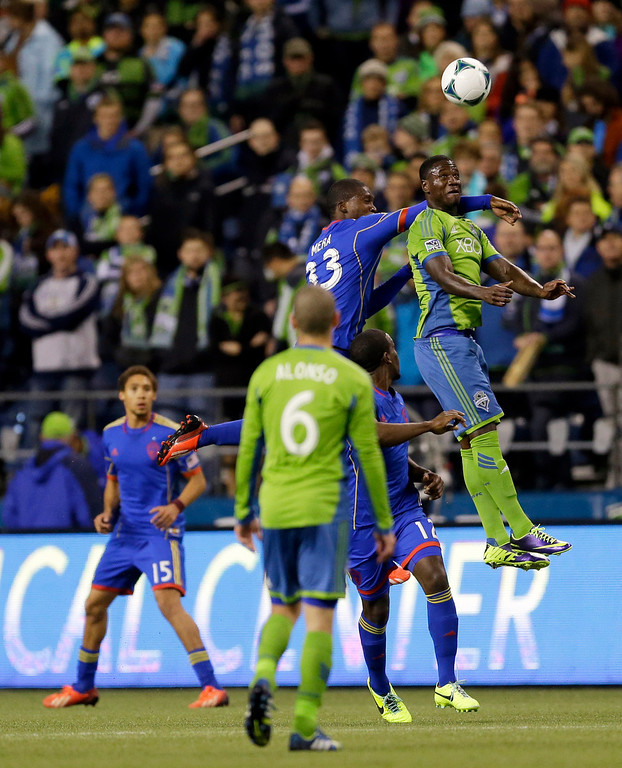 . Seattle Sounders\' Eddie Johnson, right, leaps for a header in front of Colorado Rapids\' German Mera (33) in the first half of a knockout-round match in the MLS Cup soccer playoffs Wednesday, Oct. 30, 2013, in Seattle. (AP Photo/Ted S. Warren)