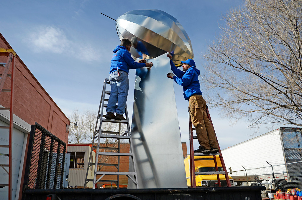 . Carlos Tovar, left, and John Darling, both employees at Frontier Roofing System in east Denver, put sheet metal on the side of a 14-foot Vince Lombardi Trophy, January, 26 2014.  (Photo by RJ Sangosti/The Denver Post)