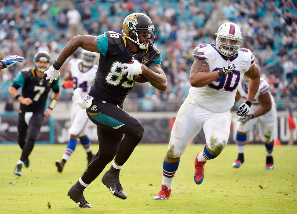 . Jacksonville Jaguars tight end Marcedes Lewis (89) runs past Buffalo Bills defensive end Alan Branch (90) for a touchdown on a 13-yard pass from quarterback Chad Henne (7) during the second half of an NFL football game in Jacksonville, Fla., Sunday, Dec. 15, 2013. (AP Photo/Phelan M. Ebenhack)