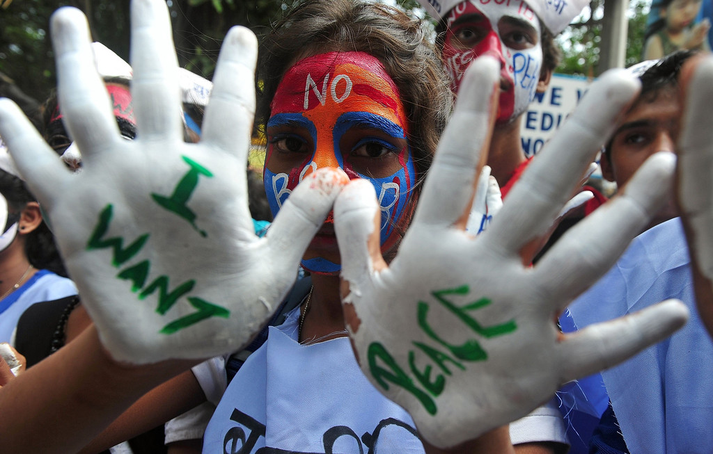 . An Indian youth, her hands and face painted with peace messages, gestures while taking part in a rally to mark Hiroshima Day in Mumbai on August 6, 2013, to mourn victims of the atomic bombing of Hiroshima in 1945.  AFP PHOTO/Indranil  MUKHERJEE/AFP/Getty Images
