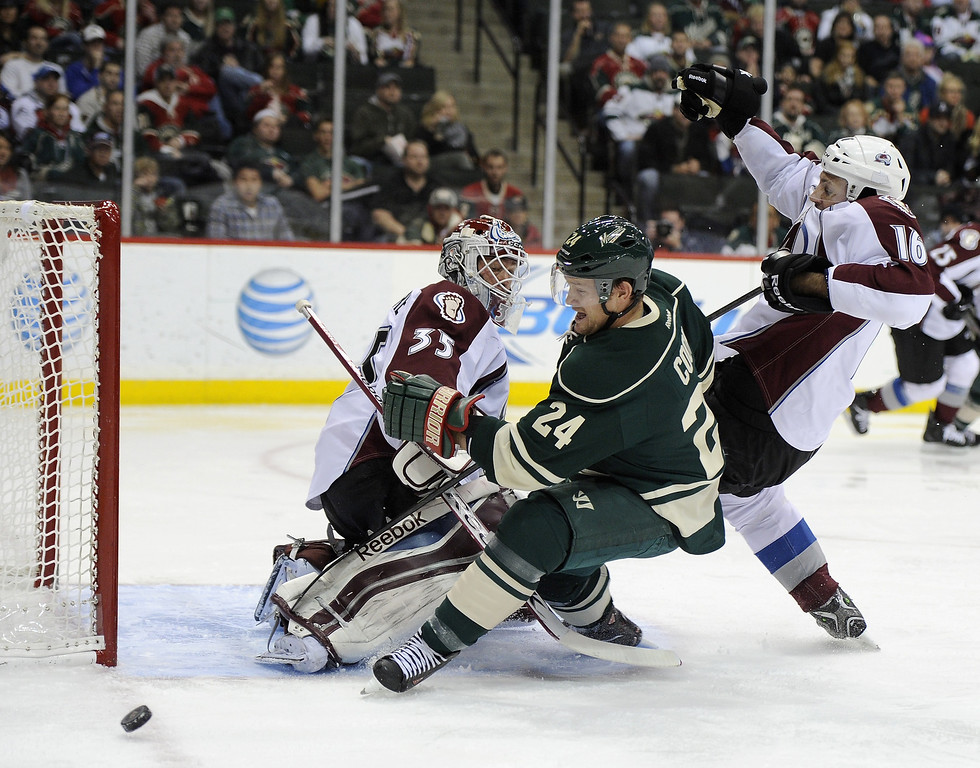 . Matt Cooke #24 of the Minnesota Wild and Cory Sarich #16 of the Colorado Avalanche skate after the puck as Jean-Sebastien Giguere #35 of the Colorado Avalanche defends the net during the second period of the game on November 29, 2013 at Xcel Energy Center in St Paul, Minnesota. (Photo by Hannah Foslien/Getty Images)