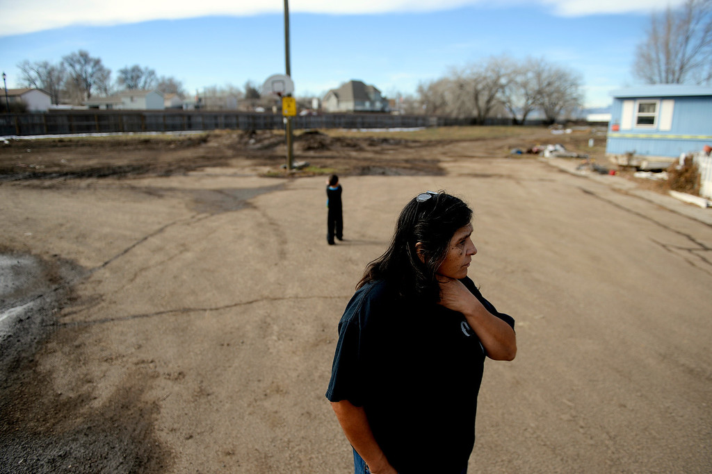 . MILLIKEN, CO - DECEMBER 18: Martha Gutierrez, manager of the Evergreen Mobile Home Park, looks surveys damage to her neighbors\' homes as her grandson, Angelo Castillo, 3, plays nearby. Residents of the mobile home park say that the city of Milliken has not done enough to assist in the rebuilding of the 33-unit residential sub division that was struck hard by recent floods that ravaged much of northern Colorado. (Photo by AAron Ontiveroz/The Denver Post)