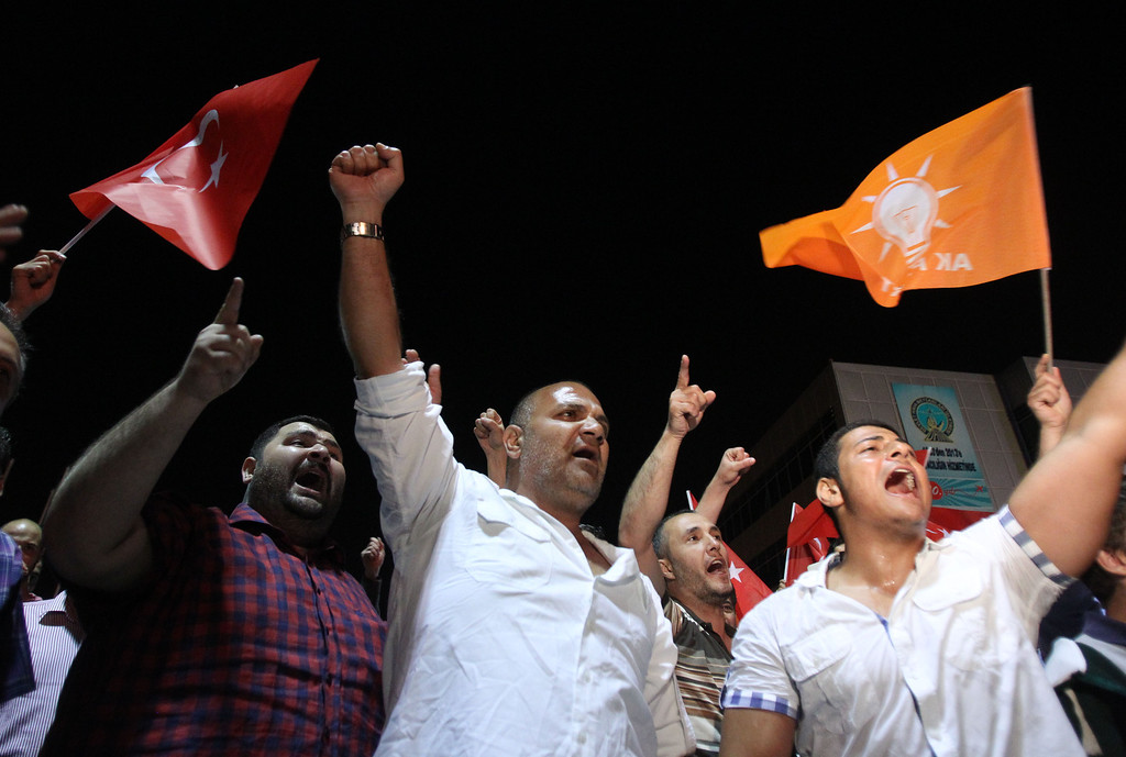. Supporters of Turkish Prime Minister Recep Tayyip Erdogan chants slogans upon his arrival at the Ataturk Airport of Istanbul early Friday, June 7, 2013. Erdogan took a combative stance on his closely watched return to the country early Friday, telling supporters who thronged to greet him that the protests that have swept the country must come to an end. In the first extensive public show of support since anti-government protests erupted last week, more than 10,000 supporters cheered Erdogan with rapturous applause outside Istanbul\'s international airport. (AP Photo/Thanassis Stavrakis)