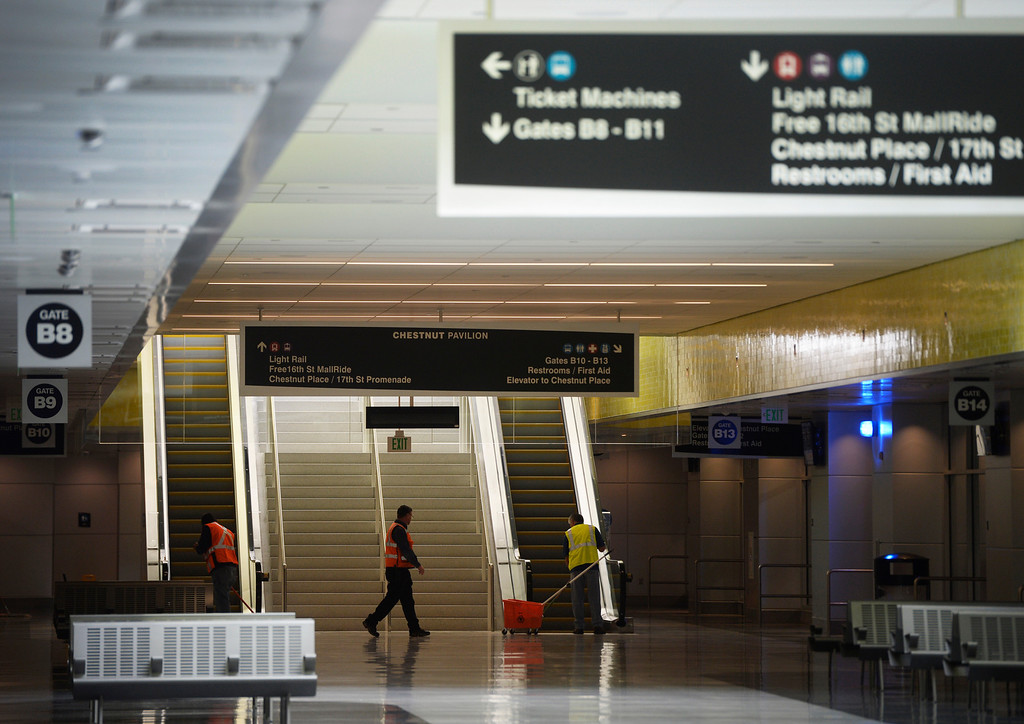 . DENVER, CO. - APRIL 25: Workers clean up in front of the Chestnut Pavilion entrance to the Underground Bus Concourse at the Union Station Transit Center during a media tour Friday morning, April 25, 2014. The transit center is scheduled to open May 11, 2014. (Photo By Andy Cross / The Denver Post)