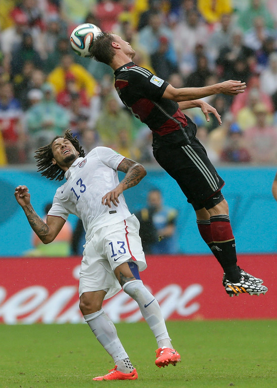 . Germany\'s Benedikt Hoewedes, right, and United States\' Jermaine Jones challenge for the ball during the group G World Cup soccer match between the USA and Germany at the Arena Pernambuco in Recife, Brazil, Thursday, June 26, 2014. (AP Photo/Matthias Schrader)