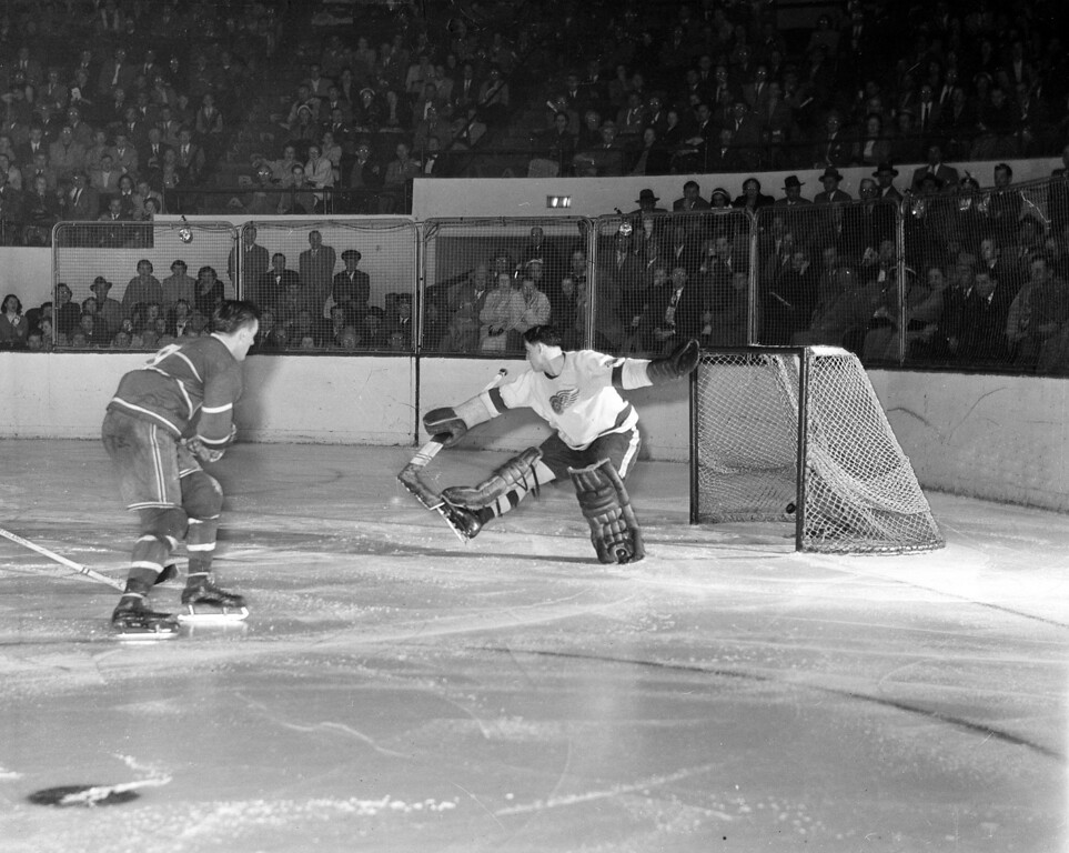 ". Montreal Canadiens forward Maurice ""The Rocket\"" Richard breaks up his second straight Stanley Cup playoffs game as he blasts the puck into the net past the Red Wings goalie Terry Sawchuck shortly after the start of the third overtime period in Detroit, Mich., March 29, 1951.  The 1-0 win put the Canadiens two games up on Detroit.  (AP Photo)"