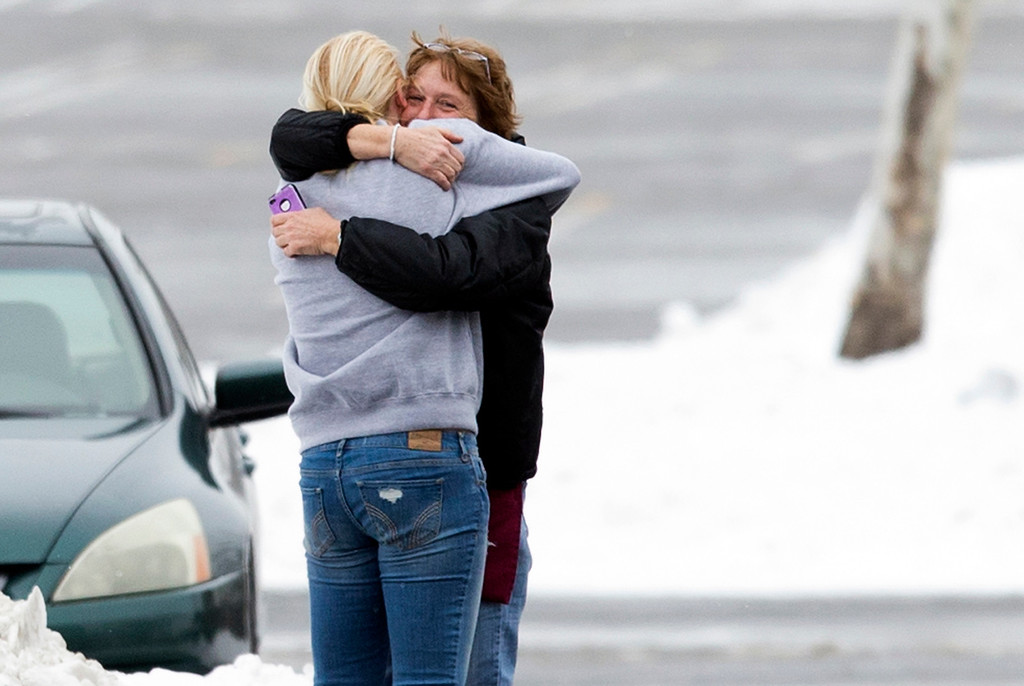 . Two people embrace in the parking lot at the scene of a shooting at The Mall in Columbia on Saturday, Jan. 25, 2014, in Columbia, Md. Police say three people died in a shooting at the mall in suburban Baltimore, including the presumed gunman. (AP Photo/ Evan Vucci)