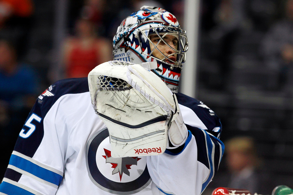 . Winnipeg Jets goalie Al Montoya talks with a referee during a break in play against the Colorado Avalanche in the second period of an NHL hockey game in Denver on Sunday, Oct. 27, 2013. (AP Photo/David Zalubowski)
