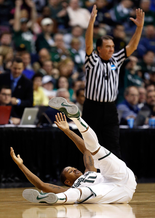 . Keith Appling #11 of the Michigan State Spartans falls to the court as the referee signals in the background in the second half against the Valparaiso Crusaders during the second round of the 2013 NCAA Men\'s Basketball Tournament at at The Palace of Auburn Hills on March 21, 2013 in Auburn Hills, Michigan.  (Photo by Jonathan Daniel/Getty Images)
