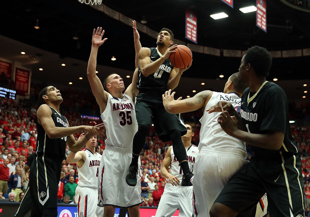 . Askia Booker #0 of the Colorado Buffaloes attempts a shot past Kaleb Tarczewski #35 of the Arizona Wildcats during the second half of the college basketball game at McKale Center on January 23, 2014 in Tucson, Arizona. The Wildcats defeated the Buffaloes 69-57.  (Photo by Christian Petersen/Getty Images)